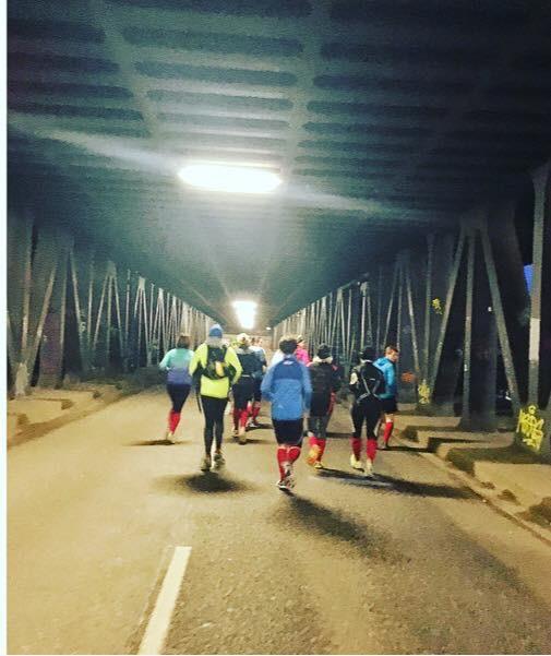 Eine Gruppe von Läufern ist von hinten zu sehen. Sie laufen durch einen beleuchteten Tunnel und tragen rote Socken (Red Socks).