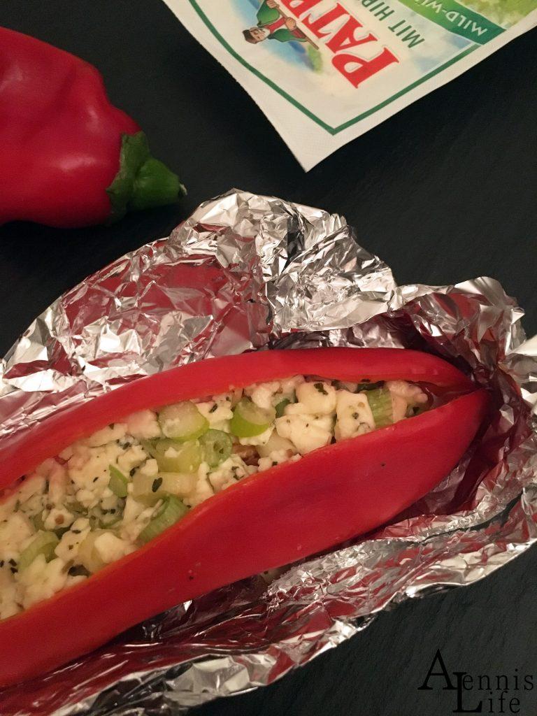 Auf dem Bild ist eine Spitzpaprika zu erkennen, welche mit Feta und Lauchzwiebeln gefüllt ist.