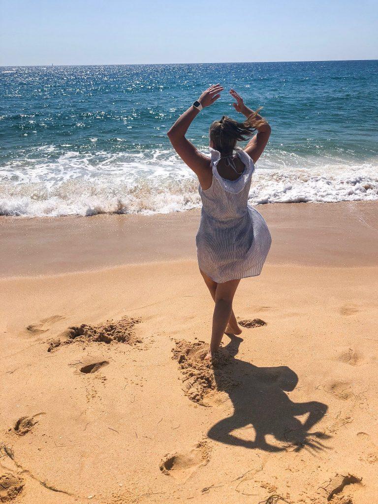 Ein Stück Strand direkt vor dem Meereswellen ist erkennbar. Annkathrin dreht im Kleid mit erhobenen Armen eine Pirouette. Man sieht Annkathrin gerade von hinten.