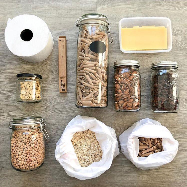Flatlay eines unverpackten Einkaufes. Verschiedene Lebensmittel sind in Gläsern oder Stoffbeuteln aufbewahrt. Dazwischen liegt eine Rolle Toilettenpapier und eine in Pappe verpackte Bambuszahnbürste.
