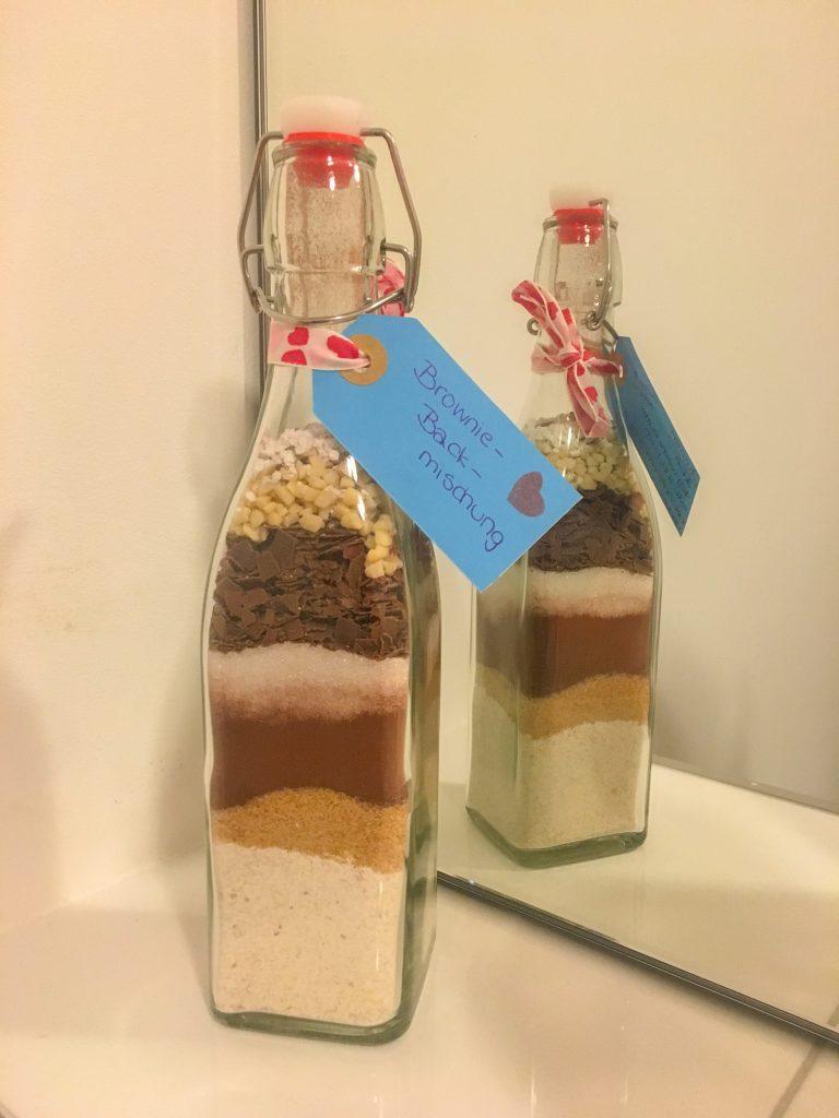 """Dies ist ein Bild einer Flasche mit Bügelverschluss, welche die Zutaten für eine Brownie-Backmischung geschichtet beinhaltet. Am Flaschenhals ist ein Geschenkanhänger auf dem """"Brownie-Backmischung"""" steht."""