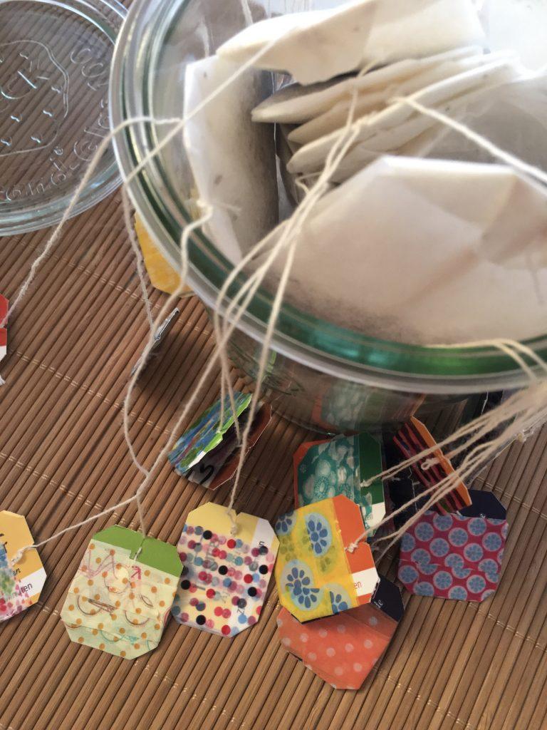Ein Glas von oben gefüllt mit Teebeuteln. Deren Anhänger hängen ausserhalb des Glases und jeder ist beklebt. Zusammen sind es 24 Stück als Tee-Adventskalender.