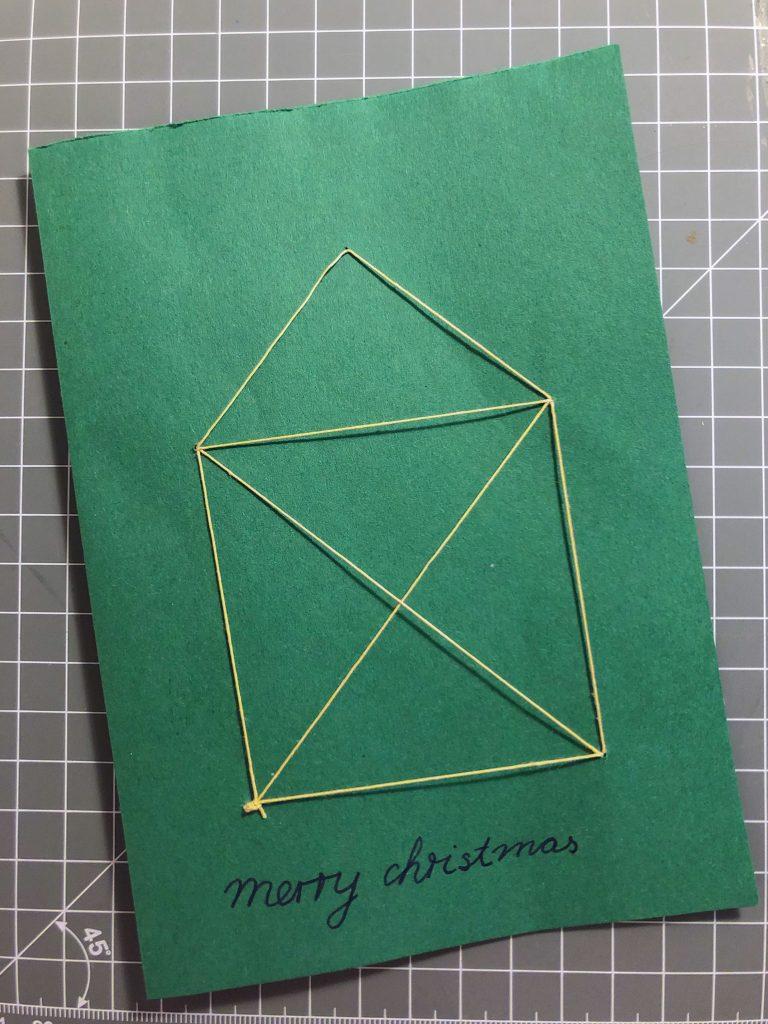 """Abgebildet ist eine grüne Klappkarte, auf der das Nikolaushaus aufgestickt ist. Dadrunter steht """" Merry Christmas""""."""