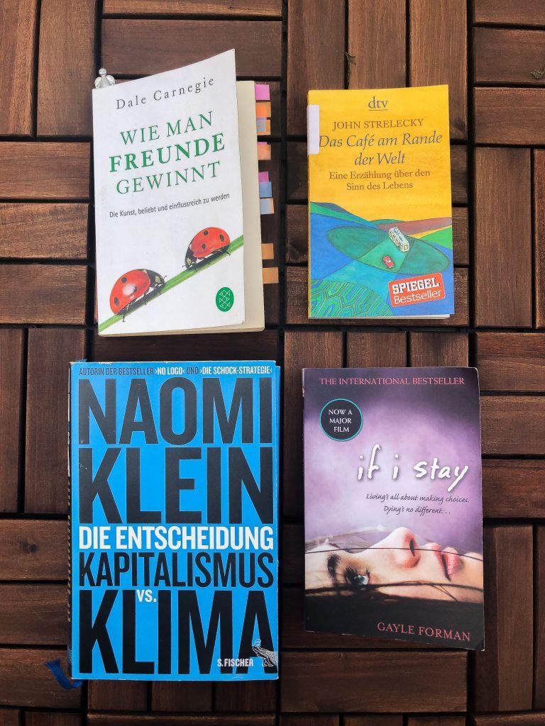 """Vier Bücher sind zu sehen. Alle vier auf Holzuntergrund angeordnet. Alle Bücher sind Bestandteil von Annkathrins Bücherliste 2019. Oben links ist """"Wie man Freunde gewinnt"""" von Dale Carnegie, links daneben """"Das Café am Rande der Welt"""" von Jan Strelecky, unten links, """"Die Entscheidung: Kapitalismus vs. Klima"""" von Naomi Klein und rechts davon """"if i stay"""" von Gayle Foreman."""